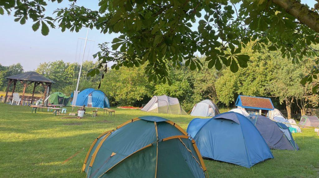 Wiese mit Zelten und Feuerstelle